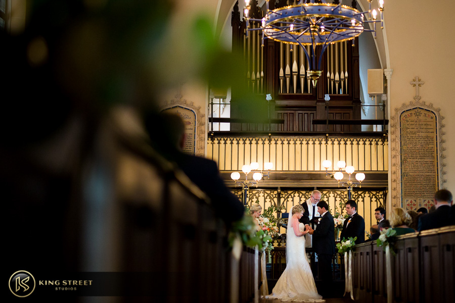 wedding pictures of bergen + philipe exchanging rings by charleston wedding photographers king street studios