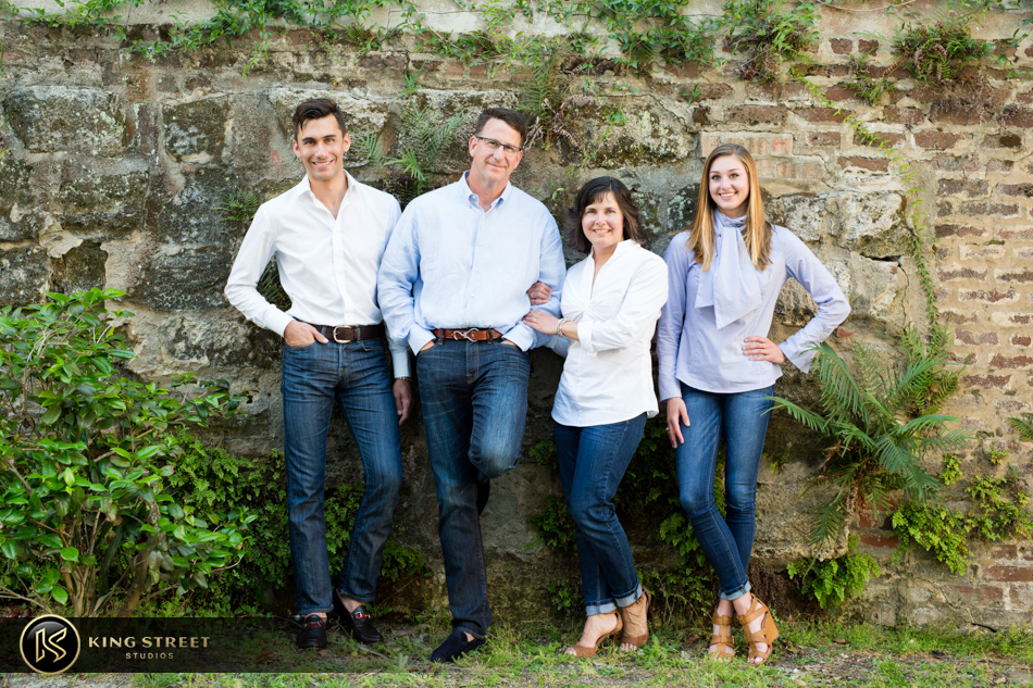 charleston family photographers king street studios photographers in charleston sc. Family sitting together in all white on a bench together with a beautiful green gardened area behind them