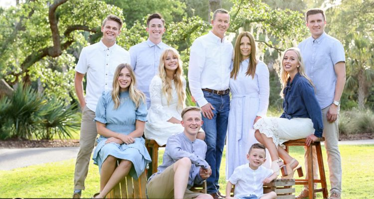 family photographers charlesron sc king street studios. Beautiful family staged on wood stools and crates on grass with sun and palm trees behind them.